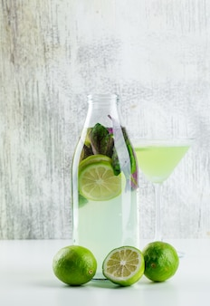 Lemonade with lemons, basil in bottle and glass on white and grungy,