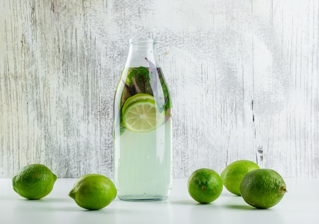 Lemonade with lemons, basil leaves in a bottle on white and grungy,