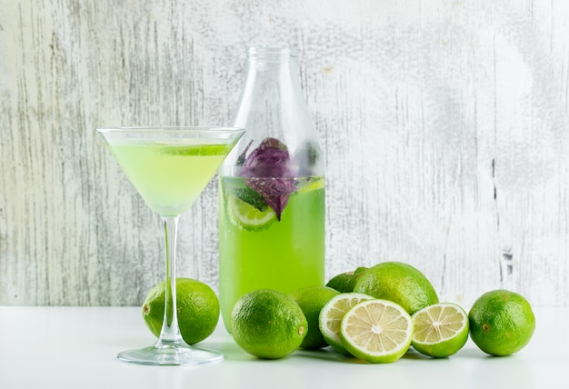 Limonata con limoni, foglie di basilico in vetro e bottiglia su bianco e sgangherata,