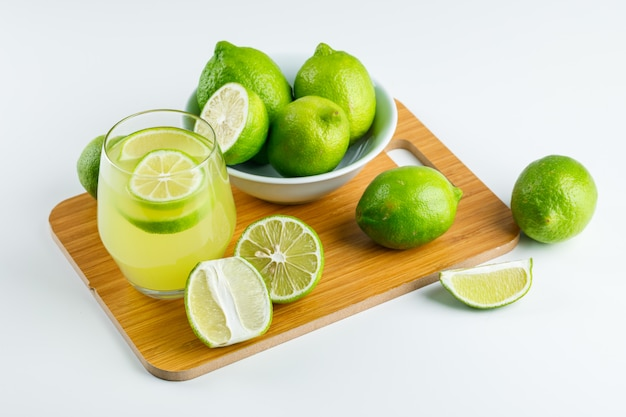 Lemonade with lemons in a glass on white and cutting board, high angle view.