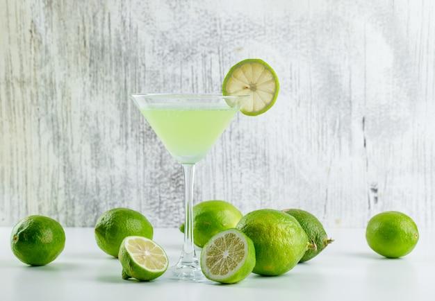 Лимонад с лимонами в стакане на белом и шероховатый,