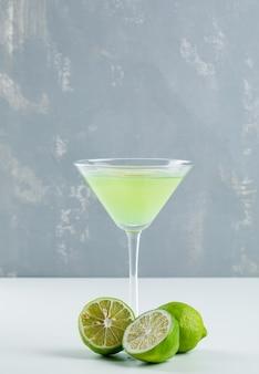 Лимонад с лимонами в стакане на белом и гипса,