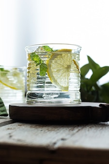 Lemonade with lemons and mint on ice on a light wooden background