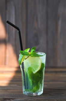Lemonade with lime, mint on a wooden table. summer drink