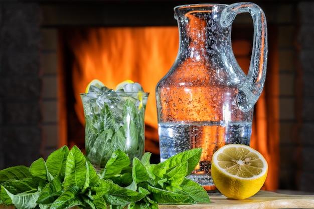 Лимонад с минеральной водой, лимоном, мятой и льдом в банке и бокале перед уютным камином.