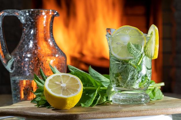 Лимонад с минеральной водой, лимоном, мятой и льдом на деревянном столе перед уютным камином. безалкогольный напиток.