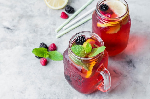 Lemonade with raspberry and blackberry with lemon, mint in mason jar.