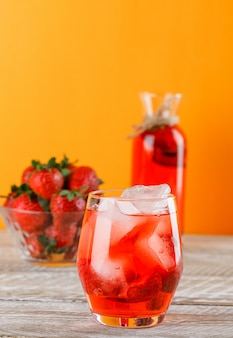 Lemonade with strawberries in jug and glass on wooden and orange wall, side view.