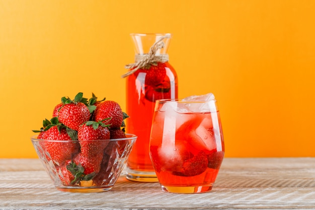 Lemonade with strawberries in jug and glass on wooden and yellow background, side view.