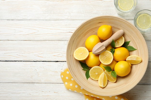 Lemonades and bowl with lemons on wooden table, top view