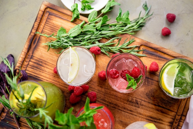 Лимонады в кувшинах на столе, ингредиенты, из которых они сделаны, расположены вокруг.