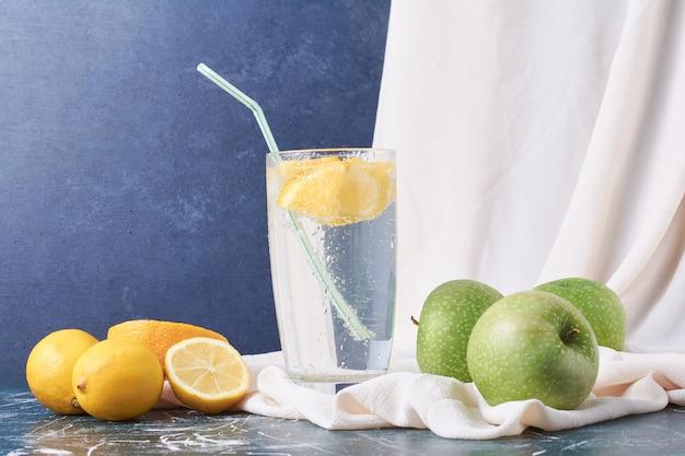 Яблоки лимона с чашкой напитка на синем.
