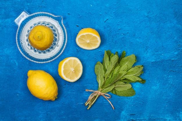 上面図のテクスチャードクラシックブルーの背景にレモンと柑橘類の絞り器