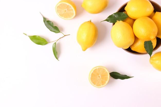 Лимоны и зеленые листья на цветном фоне. фото высокого качества