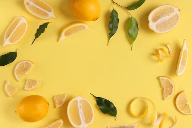 Лимоны и зеленые листья на цветном фоне