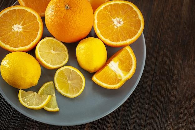 Лимоны и апельсины на тарелке на темном деревянном фоне (clouse-up)