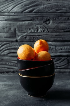Lemons in a bowl on a dark wooden background. side view. space for text