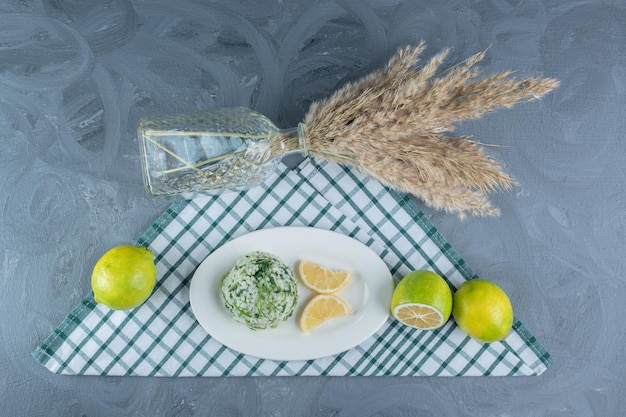 Lemons, cooked rice and decorative stalks on folded tablecloth on marble table.