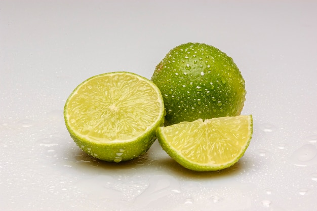 Lemons cut in half and with water droplets isolated on white background.