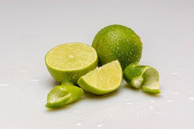 レモンは半分にカットされ、白い背景に水滴が分離されています。