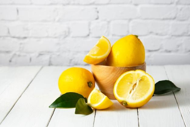 흰색 나무 테이블과 흰색 벽돌 벽 배경에 레몬 과일 구성