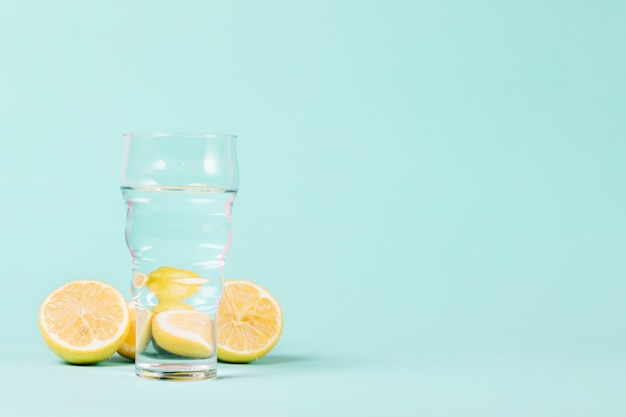 Lemons and glass on blue background