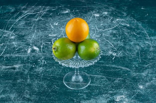 Limoni su un piedistallo di vetro, sullo sfondo di marmo. foto di alta qualità