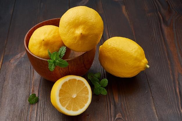Лимоны в миске на дереве