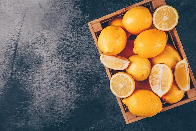 テキストの黒の織り目加工の背景の空き領域にスライストップビューで木箱にレモン