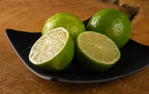 素朴な木の黒いプレートの中にレモンの詳細