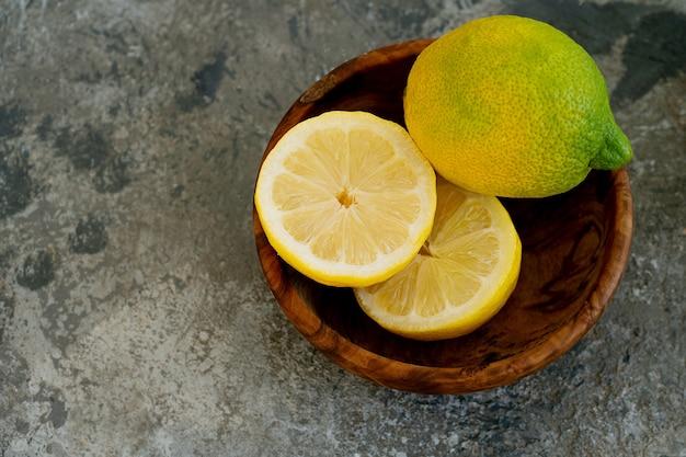Лимоны в деревянной миске. разрезать пополам. вид сверху. flat lay. копировать пространство