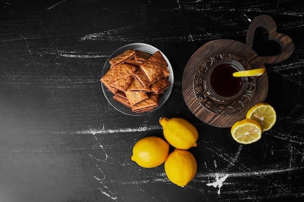 Limoni isolati su uno sfondo nero con un bicchiere di tè e cracker.