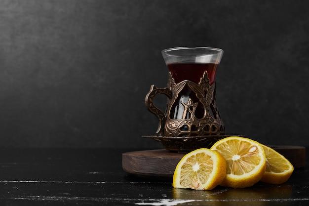 Limoni isolati su uno sfondo nero con un bicchiere di tè.