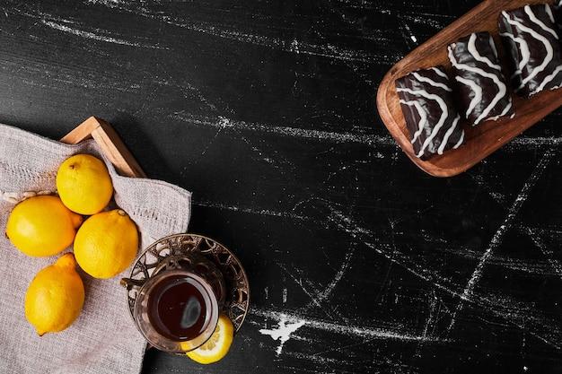 Limoni isolati su uno sfondo nero con pasticcini e tè.