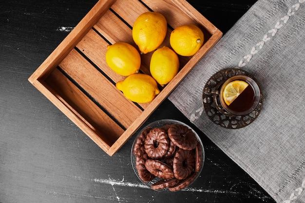 Лимоны, изолированные в деревянном подносе с чаем и шоколадным печеньем вокруг.