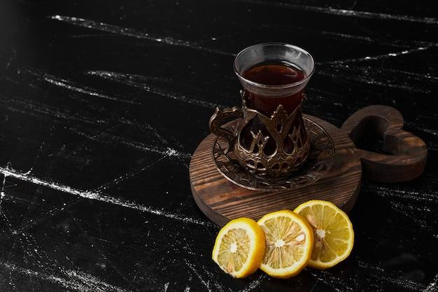 Лимоны, изолированные на черном фоне с стаканом чая.