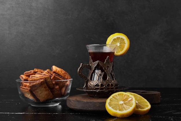 Limoni isolati su una tavola di legno con cracker e un bicchiere di tè.