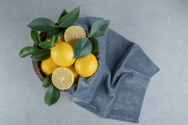 Lemons and leaves piled in a bucket on marble