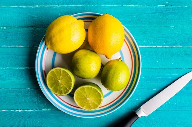 Lemons and lime on plate on table