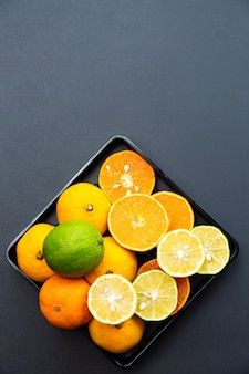 Lemons, limes and tangerines whole and halves on black plates on a black desk