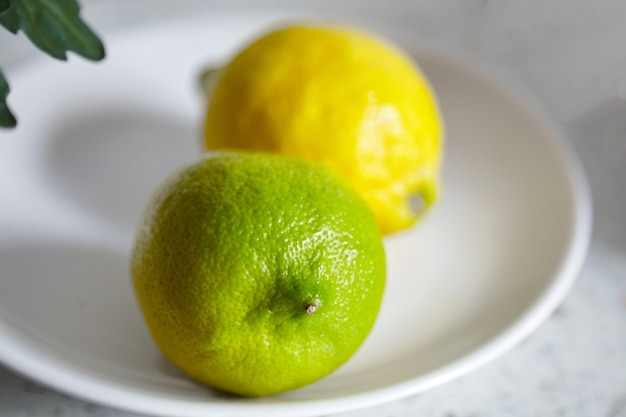 白いプレート、セレクティブフォーカスの上に横たわるレモン。背景をぼかした写真、柑橘系の果物、クローズアップに緑と黄色のレモン