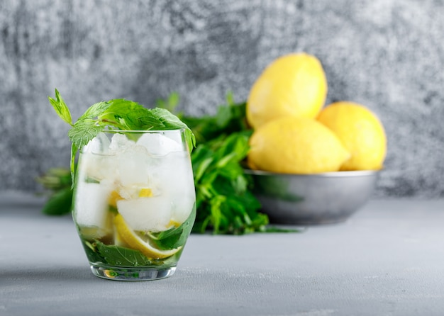 Lemons and mint in a bowl with icy detox water side view on grunge and grey surface