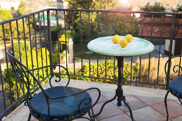 도시와 바다가 내려다 보이는 화창한 여름날 테라스에서 단조 테이블과 의자에 레몬.