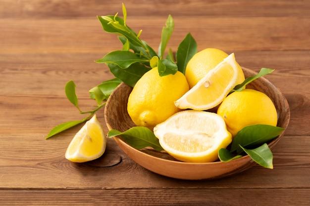 Лимоны на деревенском деревянном столе в деревянной миске