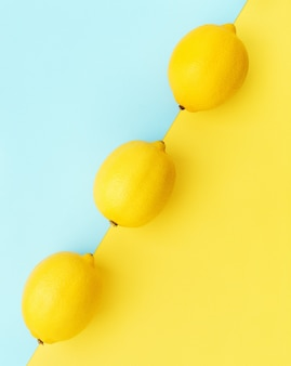 Lemons in row on pastel yellow and blue background. flat lay.