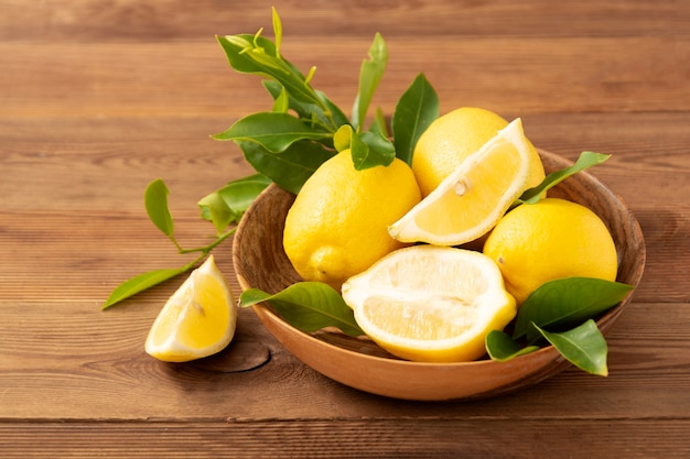 Lemons on rustic wooden table in wooden bowl