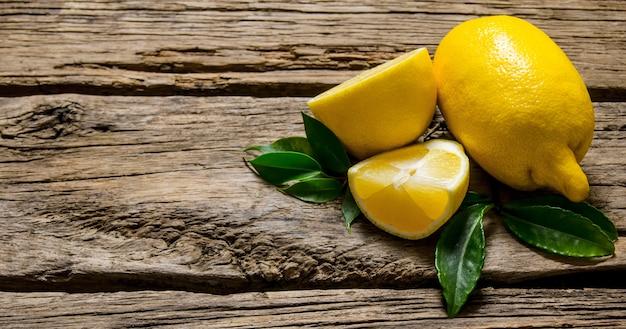 Лимоны нарезанные и целые с листьями. на деревянном фоне.