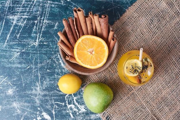 Limoni e spezie con una tazza di bevanda sull'azzurro.