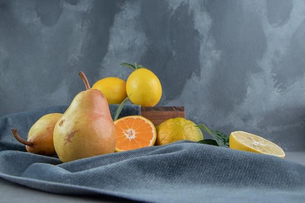 Limoni, mandarini e pere su un pezzo di tessuto su una tavola di legno, su marmo