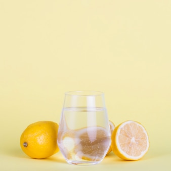 Lemons and water on yellow background